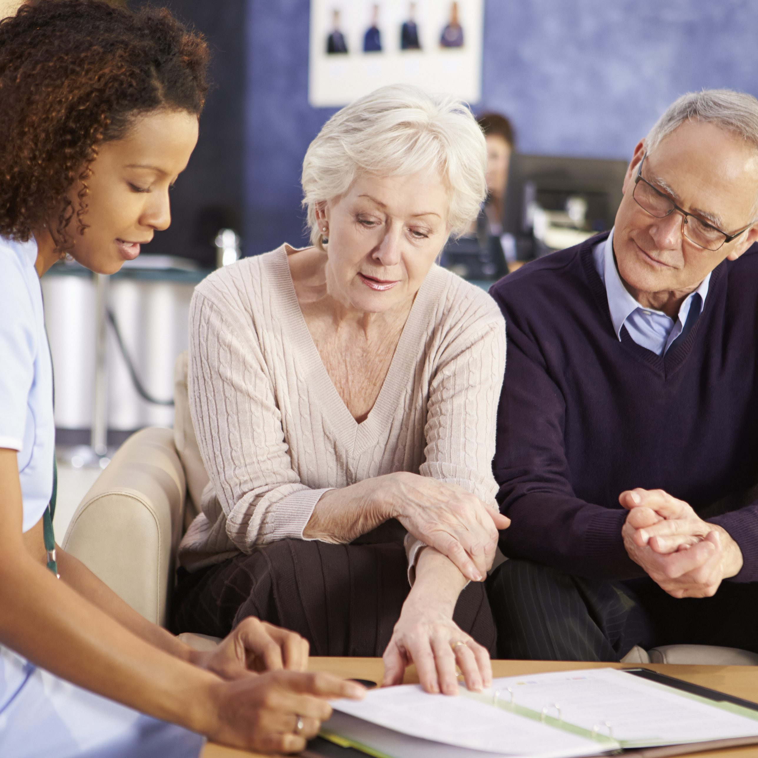 Senior Couple Meeting With Nurse In Hospital Discussing Patients Records
